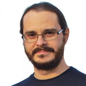 Matteo Beccati uomo con capelli corti, occhiali rettangolari, barba corta, baffi e maglietta nera