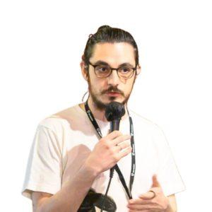 lorenzo sciandra, uomo con capelli lunghi legati dietro, occhiali,t shirt bianca e microfono in mano
